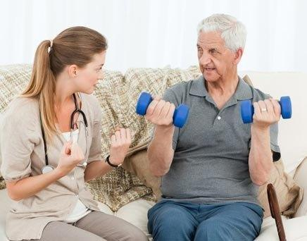 Older man exercising at home with the help of a caregiver